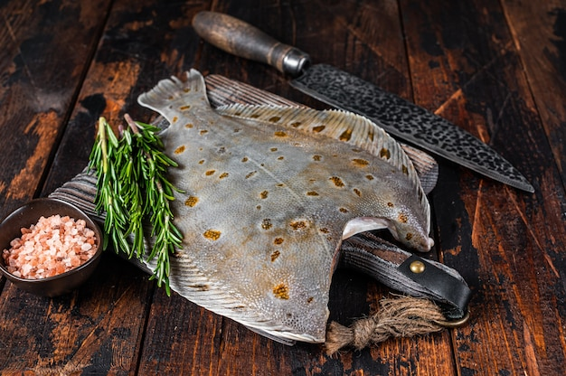 Raw plaice flatfish fish on butcher board with knife. dark wooden background. top view.
