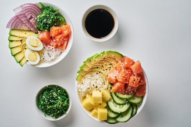 Raw poke bowl with with rice, avocado, salmon, mango, quail eggs