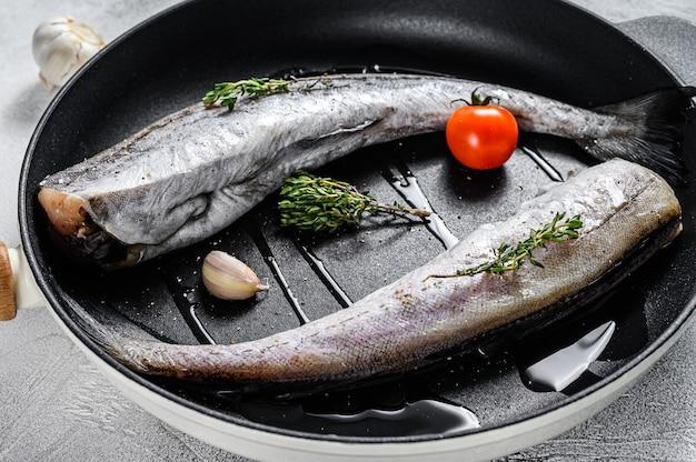 鍋に生のポロック魚。有機シーフード。灰色の背景。上面図。