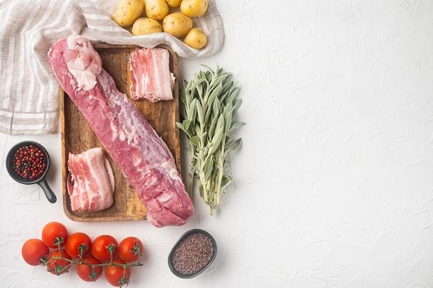 Набор ингредиентов для запекания из сырой свинины и пюре, на деревянном подносе, на белом камне