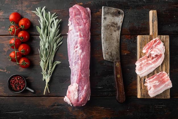 Сырая свинина и ингредиенты запеканки, установленные старым ножом для мясника, на старом темном деревянном столе