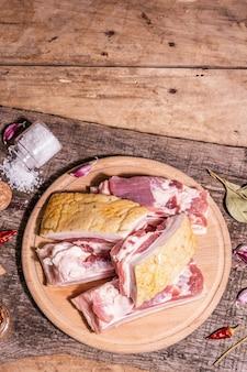 皮、腹膜肉を添えた生の豚バラ肉。スパイスやハーブ、健康的な食事を調理するための材料、動物性タンパク質。ヴィンテージ木製テーブル、上面図