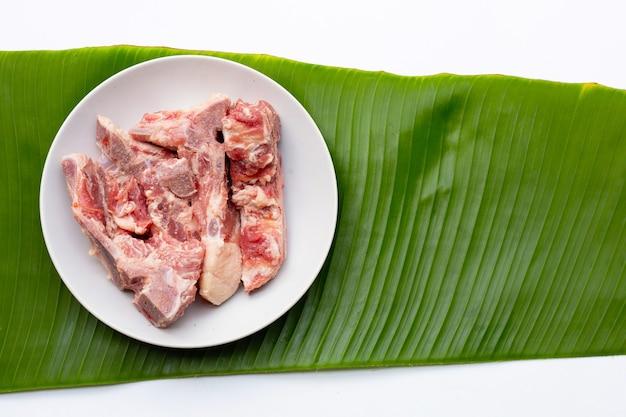 흰색 바탕에 바나나 잎에 흰색 그릇에 원시 돼지고기 뼈.