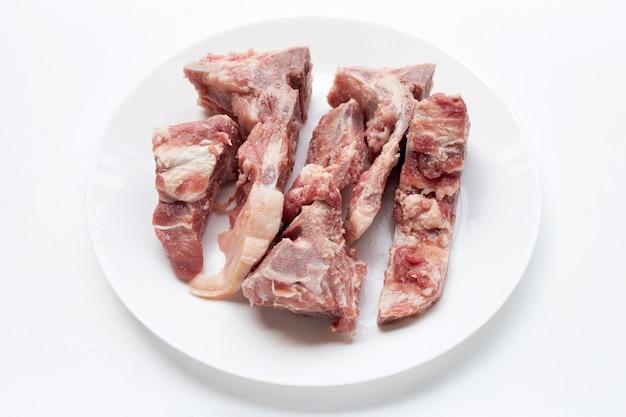 흰색 배경에 흰색 접시에 원시 돼지 뼈.
