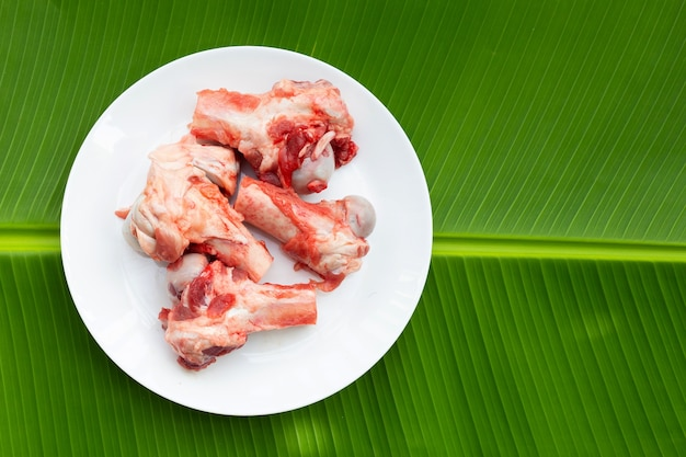 Raw pork bones in white plate on banana leaf