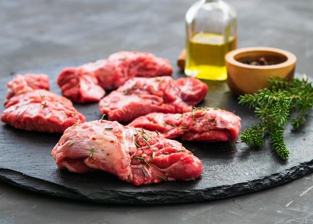 원시 돼지 고기 뺨 고기 로즈마리와 향신료와 어두운 배경에.