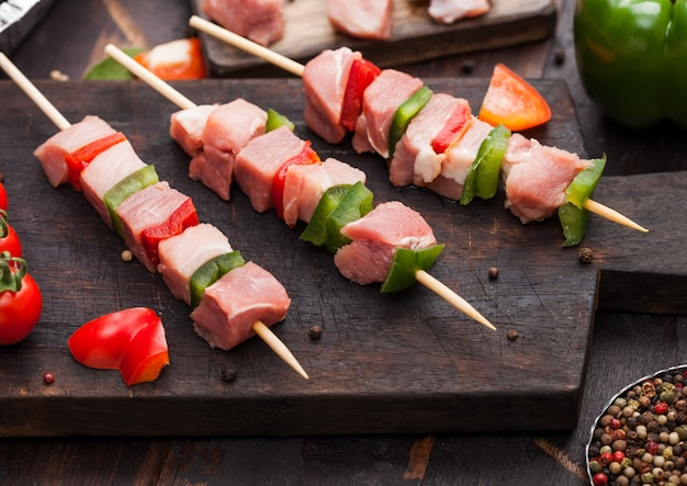 Raw pork and chicken kebab with paprika on chopping board with salt and pepper on wood.