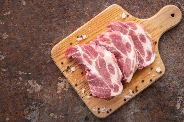 녹슨 질감 배경에 있는 나무 커팅 보드에 소금과 후추를 넣은 생 돼지고기 필렛, 텍스트 복사 공간, 위쪽 보기
