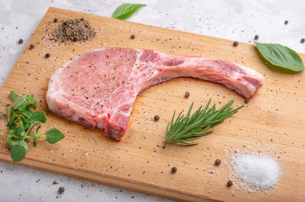 로즈마리 오레가노 소금 후추와 바질을 곁들인 커팅 보드에 생 돼지고기