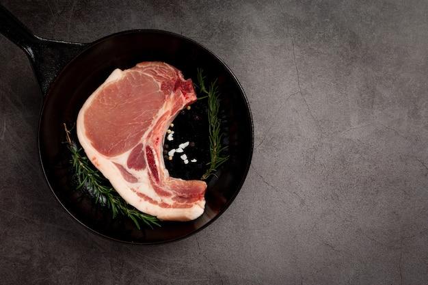 Bistecca di braciola di maiale cruda sulla superficie scura.