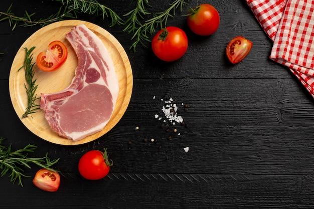 Bistecca di braciola di maiale cruda sulla superficie di legno scuro.