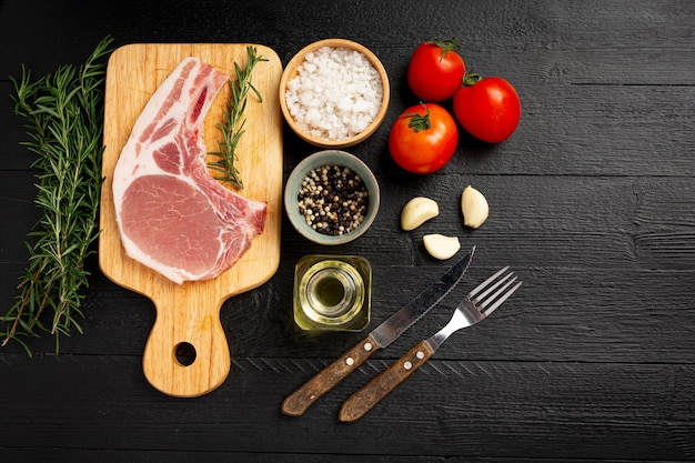 어두운 나무 표면에 원시 돼지 고기 스테이크.