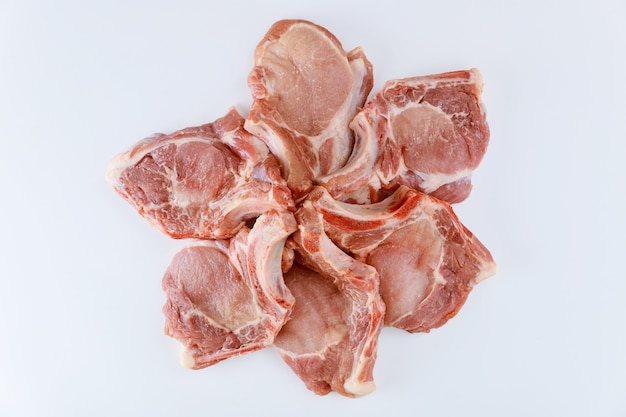 Сырые свиные отбивные кость в изолированном на белой поверхности. вид сверху.