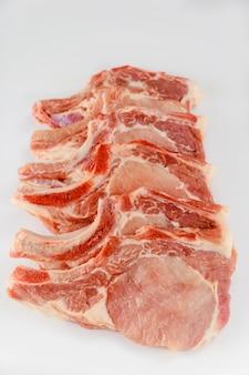 生の豚肉は、白い背景で隔離の骨をチョップします。