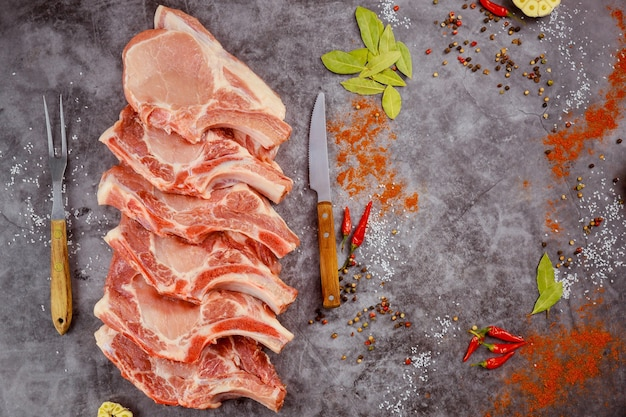 生の豚肉は暗い背景にスパイスで骨を切り刻みます。上面図。