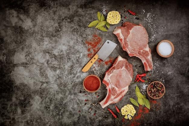 Сырые свиные отбивные со специями и тесаком на темной поверхности