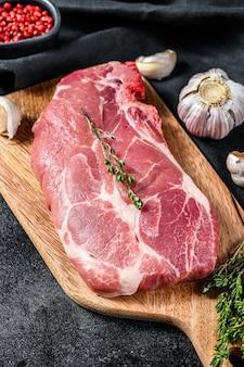 Стейк котлеты сырой свинины. готовый к приготовлению кусок сырого мяса с зеленью и специями. черный фон. вид сверху.