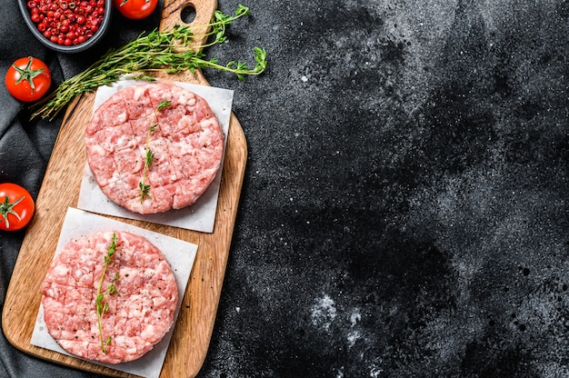 Raw pork cutlets, ground meat patty on a cutting board. organic mince. black background. top view. copy space.