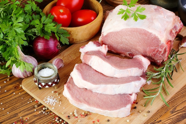 Raw pork fillet on a cutting board, cut into steaks