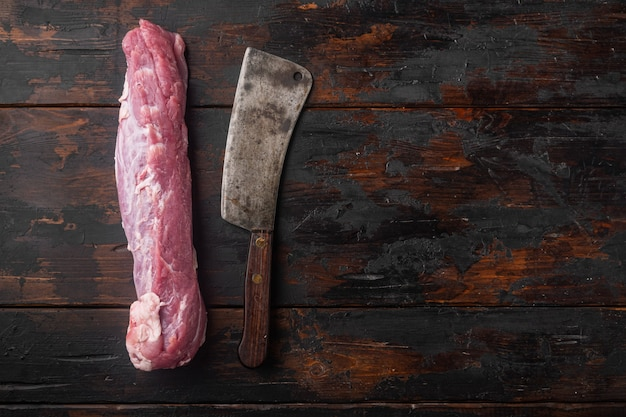 Сырое филе свинины со старым мясным ножом на старом темном деревянном столе