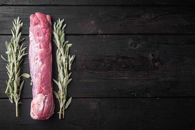 Raw pork fillet tenderloin. fresh meat with ingredients and herbs for grill or baking, sage, potatoe set, on black wooden table background, top view flat lay , with copyspace  and space for text