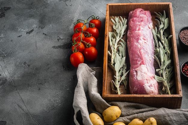 Сырое филе свинины с набором шалфея, в деревянной коробке, на сером камне