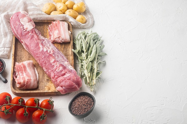 Raw pork fillet with sage set, on wooden tray, on white stone  background , with copyspace  and space for text