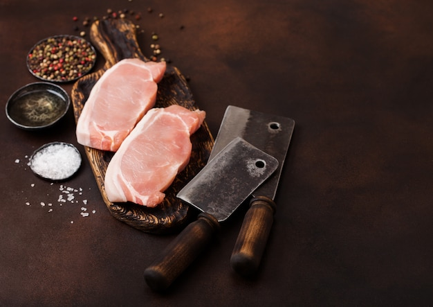 Сырые свиные корейки на старой винтажной разделочной доске с ножом и вилкой