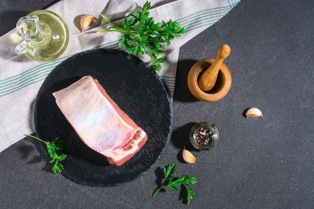 灰色の背景の黒いプレートに生の豚ロース肉