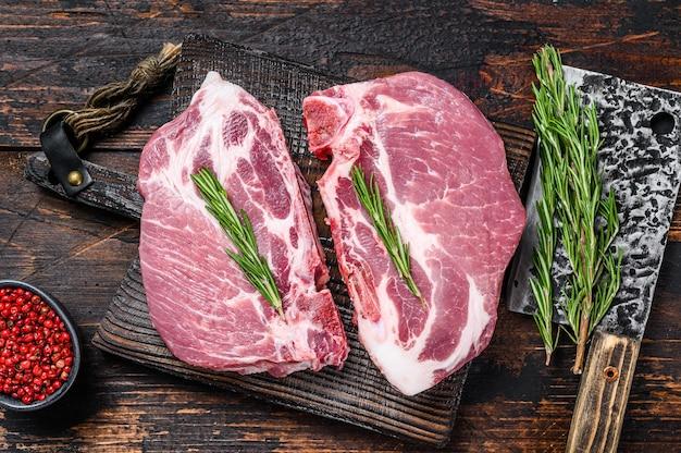 肉切り包丁のまな板にハーブを添えた生豚ロースステーキ。暗い木の背景。上面図。
