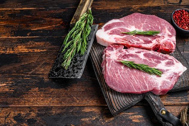 Сырые стейки из свиной корейки с зеленью на разделочной доске с ножом для мяса
