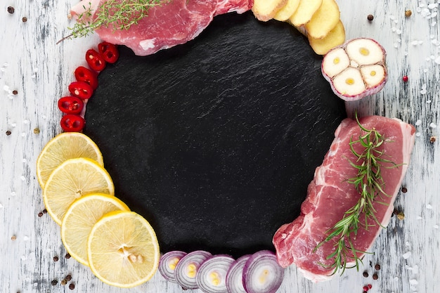 Raw pork meat on black slate plate with spice ingredient - rosemary, ginger, chilli pepper, onion,top view, flat lay, copy space,