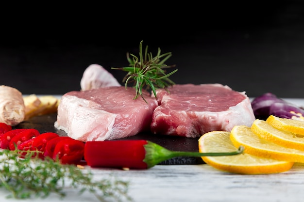 Raw pork meat on black slate plate with spice ingredient - rosemary, ginger, chilli pepper, onion.