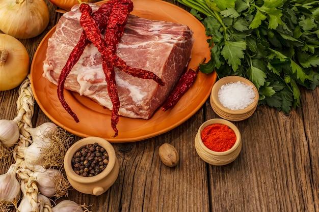 生の豚肉。新鮮なロース、スパイス、香りのよい野菜、パセリ