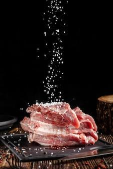 원시 돼지 고기는 부엌 칼 옆 나무 테이블에 커팅 보드에 놓여 있습니다. 향신료에 절인 고기. 배경 이미지.
