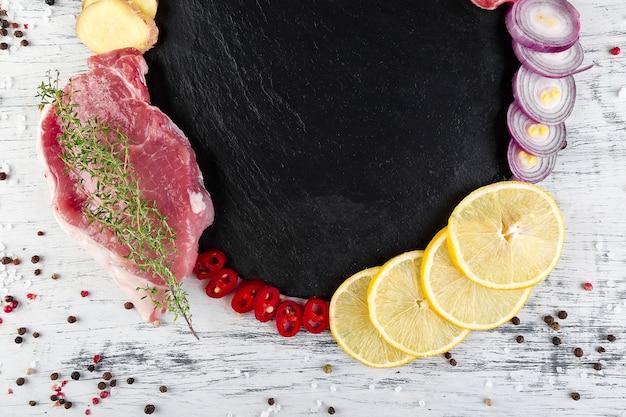 Сырое мясо свинины на черный сланец пластины с ингредиентом специи - розмарин, имбирь, перец, лук. вид сверху. квартира лежала. копировать пространство