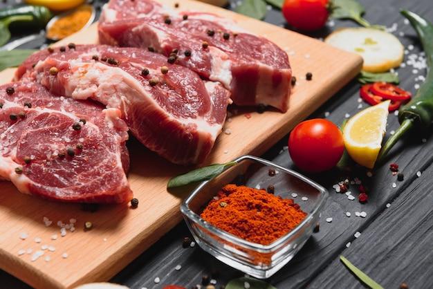 Сырое мясо свинины на деревянной разделочной доске на кухонном столе для приготовления стейка из свинины, запеченного или приготовленного на гриле с ингредиентами, травами и специями, свежая свинина