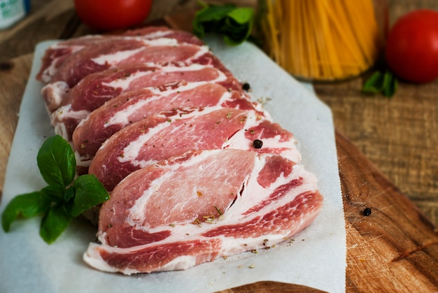 Raw pork meat with spices, on cutting board.