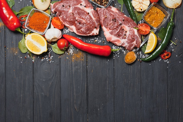 Raw pork meat with spices and vegetables on wooden table