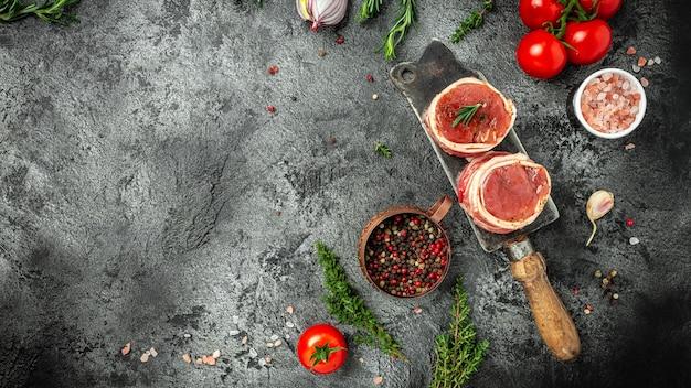 ベーコンに包まれた生のポークメダリオンステーキは、スパイスの塩とコショウで暗いコンクリートの背景に古い肉屋で提供されます。長いバナー形式、上面図。
