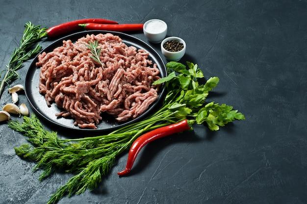 Raw pork minced on a black plate.