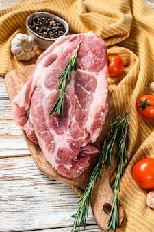 Сырая свиная вырезка из свиной шеи с зелеными листьями и специями