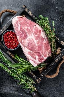 허브와 함께 나무 쟁반에 잘라 스테이크를위한 원시 돼지 목 고기 조각