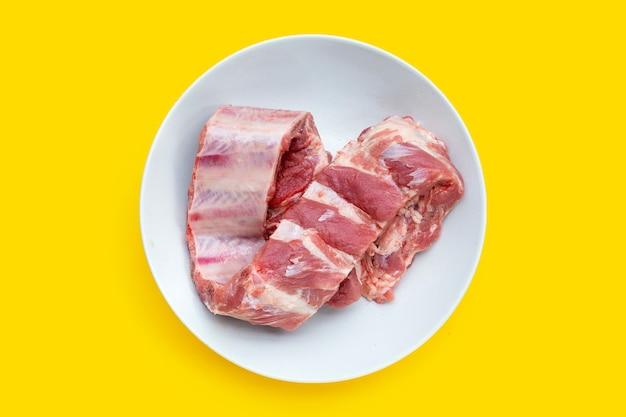 노란색 배경에 흰색 접시에 생 돼지 갈비.