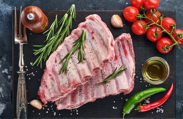 Сырые свиные ребрышки или свежее сырое мясо со специями на черном деревянном подносе с паприкой, зубчиками чеснока и зеленью. темный текстурированный фон с копией пространства для текста.
