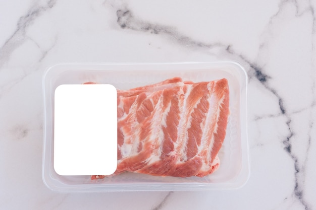 Raw pork ribs in vacuum packaging on marble background, logo mockup for design.