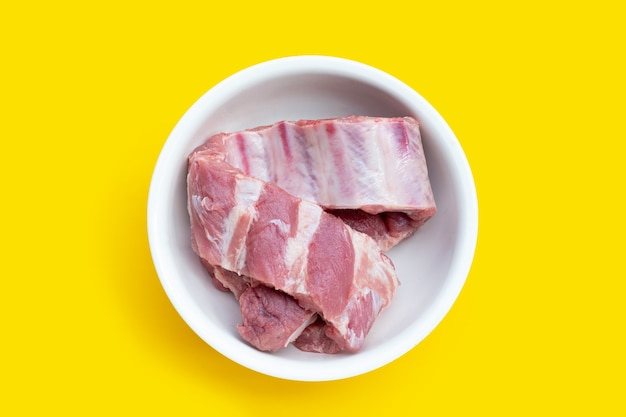 Raw pork ribs in white bowl on yellow background.