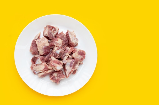 Raw pork ribs in white plate on yellow background.