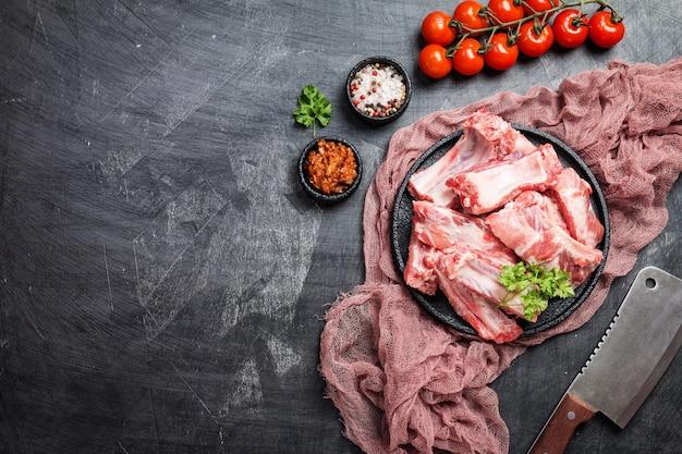Сырые свиные ребрышки с соусом и специями на черном
