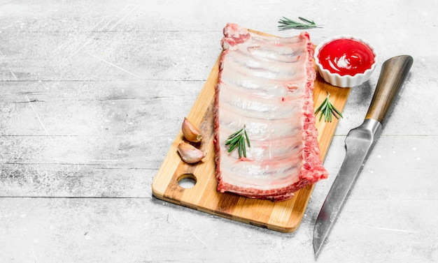 향신료와 소스를 곁들인 생 돼지 갈비. 소박한 테이블에.